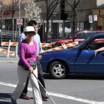 Visually impaired woman with a cane crossing with O&M instructor